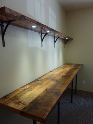 "Standing Desk with shelf and recessed LED puck lights on a dimmer switch; Reclaimed barn wood, black gas pips, LED puck lights; 108"" x 23"" x 30 1/4""; 2015; Meg Thompson"